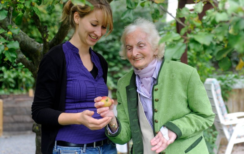 eine Betreuungssituation von Herbst-Zeitlos e.V. mit einer älteren Frau am Baum
