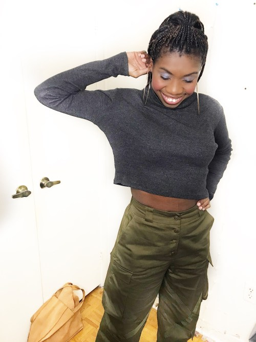 Telly smiles wearing her olive green combat pants