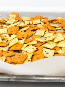 cheez-its covered in oil, ranch packet, and red pepper flakes on baking sheet