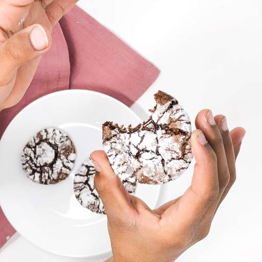 kid holding gooey crinkle brownie cookies covered with powdered sugar with a white plate and pink napkin