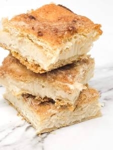 Three sopapilla cheesecake bars stacked on top of each other on top of a white marble surface.