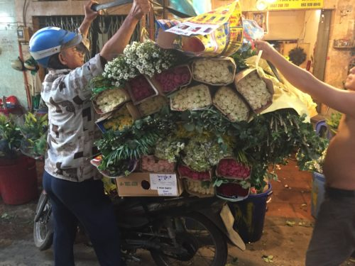 Buyer loading motorbike with fresh flowers in Vietnam