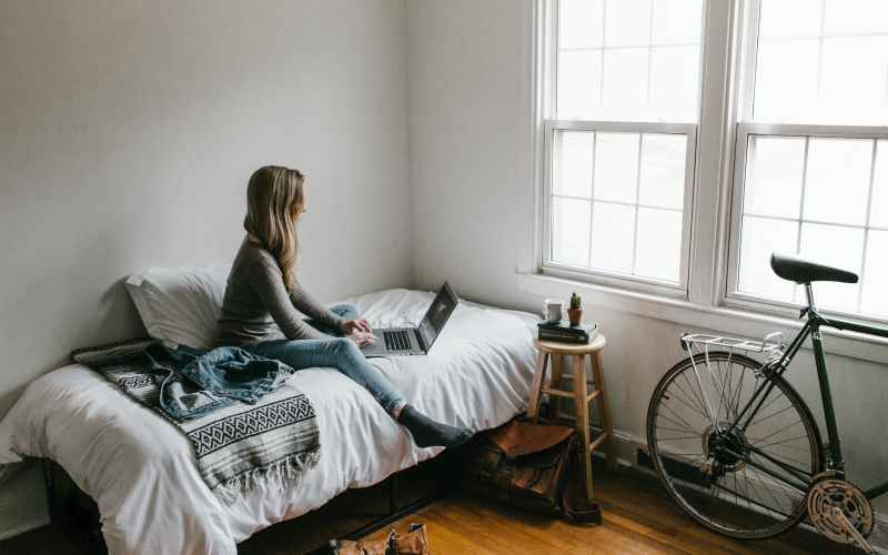 Woman typing on computer on bed