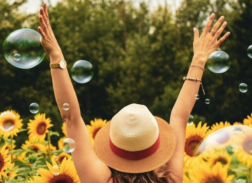woman happily running through sunflowers and bubbles