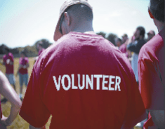 Back of man with shirt that reads volunteer