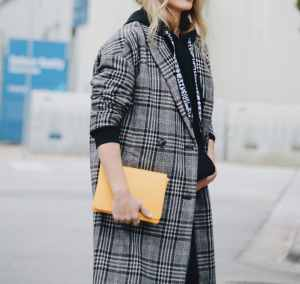 Proenza Hoodie styled with plaid jacket and yellow clutch - Her Fashioned Life