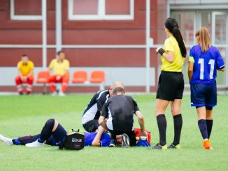 Women football player lying injured on ground, while medic team helping her.