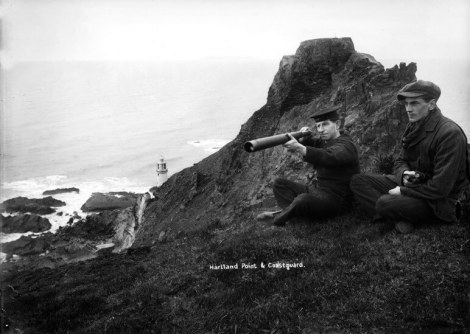 A Coastguard and friend watching from the cliffs near Hartland Point, Devon. A lighthouse is just visible in the distance while in the vicinity, but out of view, is a signal station latterly a Coastguard station.