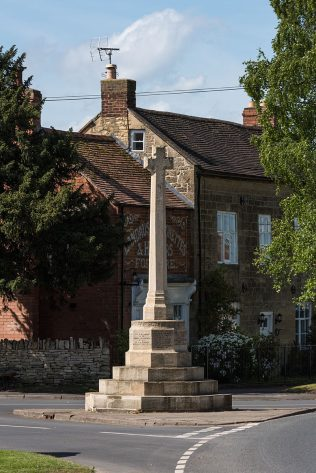 Kemerton War Memorial, Worcestershire. Unveiled 9 January 1921. Newly listed at Grade II. This limestone memorial cross, standing in the High Street at a road junction, commemorates the 20 local servicemen who died in the First World War. The biblical quote from John 15: GREATER LOVE HATH NO MAN THAN THIS and the date 1914 + 1919 are carved in relief around the top of the plinth, with the names of the fallen inscribed on the sides.