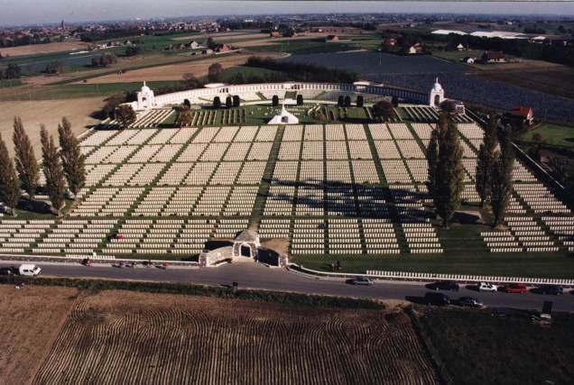 Tyne Cot Memorial, near Ypres, Belgium. Unveiled 20 June 1927. After the Armistice of 11 November 1918, Tyne Cot was formally established as a military cemetery under the auspices of the Imperial (now Commonwealth) War Graves Commission (CWGC), with Herbert Baker commissioned as designer and architect. Tyne Cot, or 'Tyne Cottage', was the name given by the Northumberland Fusiliers to a German pill box complex near Passchendaele in the Ypres salient, eventually captured by British and Empire forces October 1917. The largest pill box became a dressing station for casualties, and the 343 who died from their injuries were buried nearby. After the war's end, the authorities decided to consolidate all the graves in the region, and the remains of thousands of soldiers were brought to Tyne Cot for re-interment from the battlefields of Passchendaele and Langemarck, and from nine other small burial grounds. There are now 11,961 British and Commonwealth servicemen of the First World War buried or commemorated at Tyne Cot. 8,373 of the burials are unidentified and these graves bear the moving words: 'A SOLDIER OF THE GREAT WAR/KNOWN UNTO GOD.' This is largest of the Commission's cemeteries reflecting the bitter fighting which took place around Ypres from October 1914 to October 1918. The cemetery's curved north-eastern perimeter wall is the Memorial to the Missing where the names of 34,959 men who have no known grave are inscribed. Reginald Blomfeld's Cross of Sacrifice with its embedded reversed bronze sword – found in most CWCG cemeteries – was erected on the original large German pillbox/dressing station at the suggestion of George V (the Queen's grandfather) when he visited the cemetery in 1922 while it was being created.