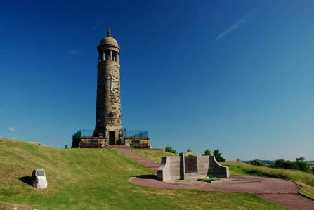 Crich Stand Memorial Tower, Derbyshire. Unveiled 6 August 1923. Upgraded to Grade II* Copywright Rob Bendall. Crich Tower is a regimental memorial to the 32 battalions of the Sherwood Foresters who fought in the First World War and particularly honours the 11,409 men of all ranks who died. The circular tower - with a large stone cross inset on its face, along with the Sherwood Foresters' insignia - is built high on the summit of Crich Hill. It stands nearly 20 metres tall and, unusually for a war memorial, has a viewing platform. In 1934, the tower was fitted with a large revolving searchlight whose beam has a range of 38 miles.