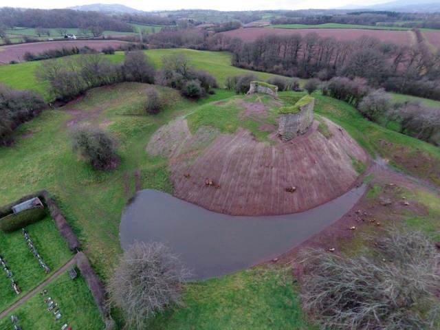 The motte and bailey castle at Kilpeck in Herefordshire. The remains of a stone curtain wall, added in the 12th century, can be seen on top of the motte.