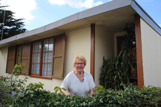 A woman stood in front of her prefab house
