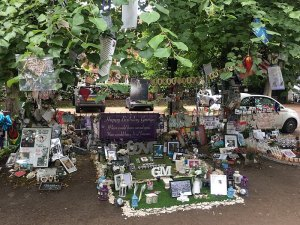 A memorial to garden to George Michael with flowers, gifts and notes