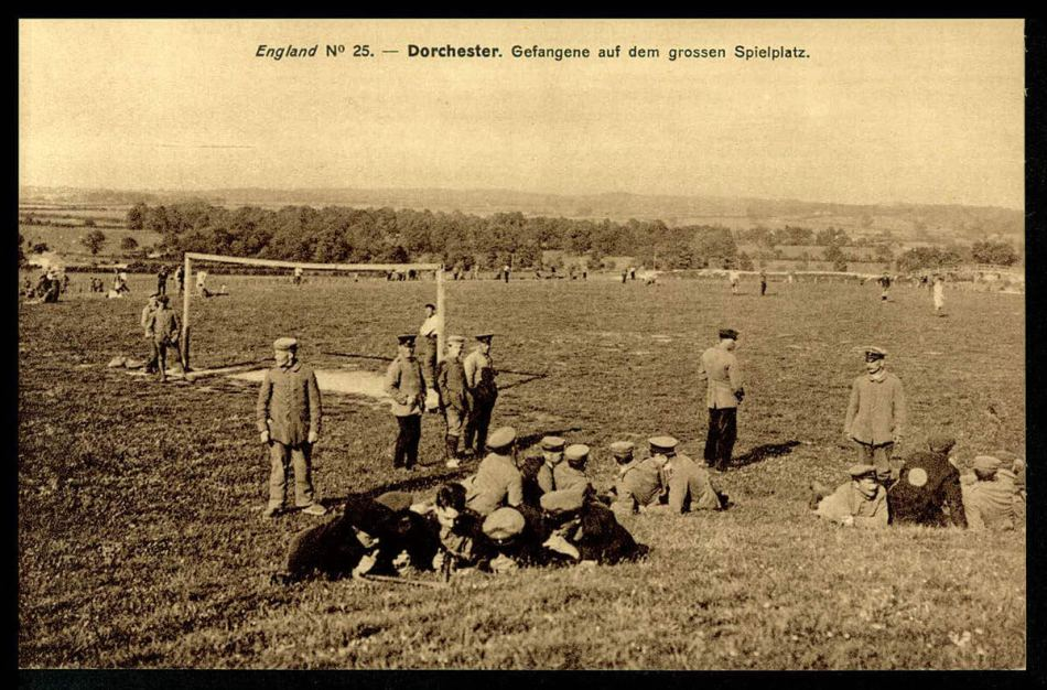 POWs at a sports ground, with a footbal net in the background, some are lazing on the grass and others are stood chatting