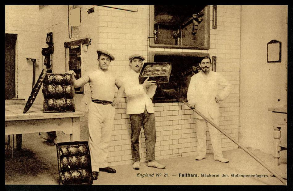 Three POW bakers stand near an oven, two holding bread