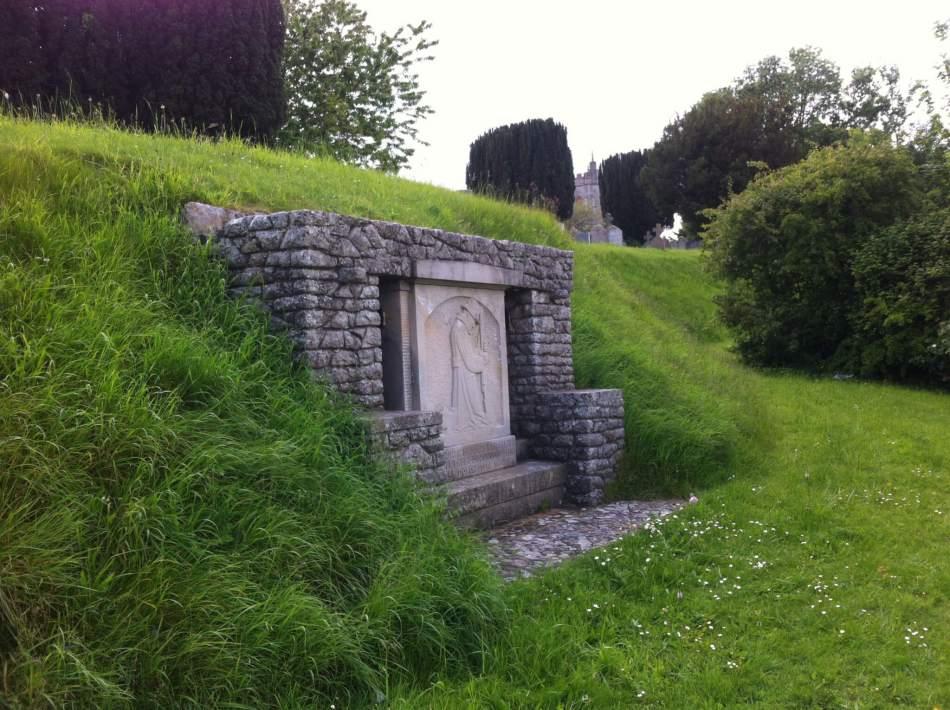 A stone German POW war memorial set into a grass verge.