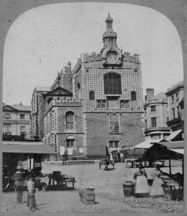 Black and white image of Norwich Guildhall with produce stalls and people in the foreground