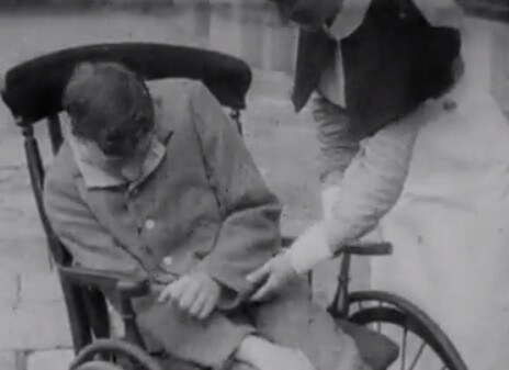 A man in a wheelchair is assisted by a nurse