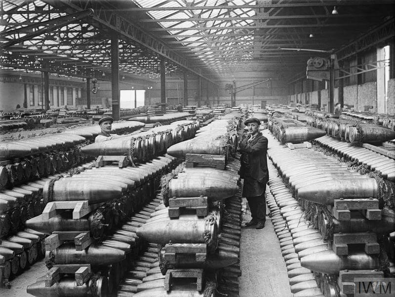 Two men stand beside multiple rows of stacked shells