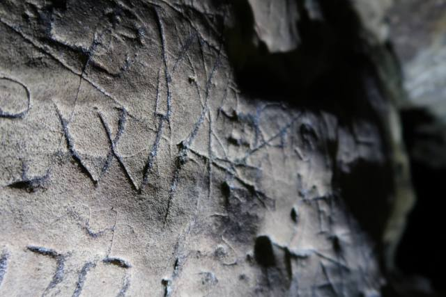 Close up of Creswell Crags wall markings reading 'VV'