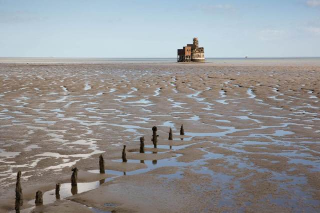 Grain Tower seen in the distance on a sand bank at low tide