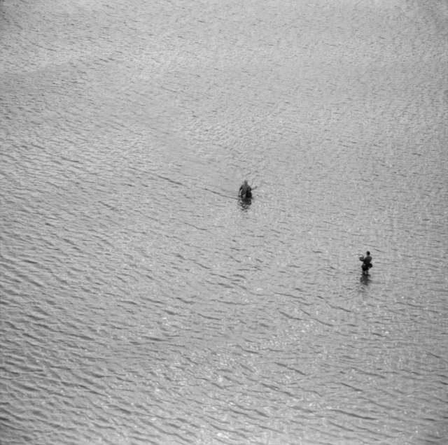 Two men are seen from above, both stood in the river with the water up to their knees. One man is photographing the other