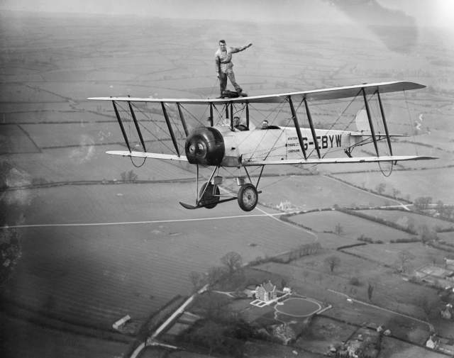 Martin Hearn wing walking on Aviation Tours Ltd Avro 504K G-EBYW - he looks to be holding onto the wing of the plane by a rope held in his right hand, his left hand held aloft