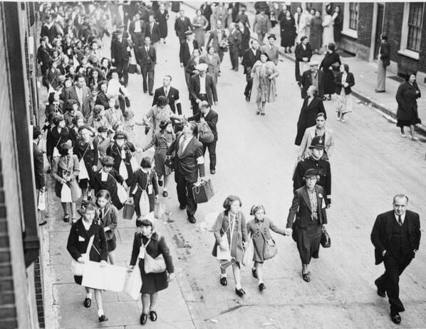 Children walk along the street carrying suitcases and gas mask boxes