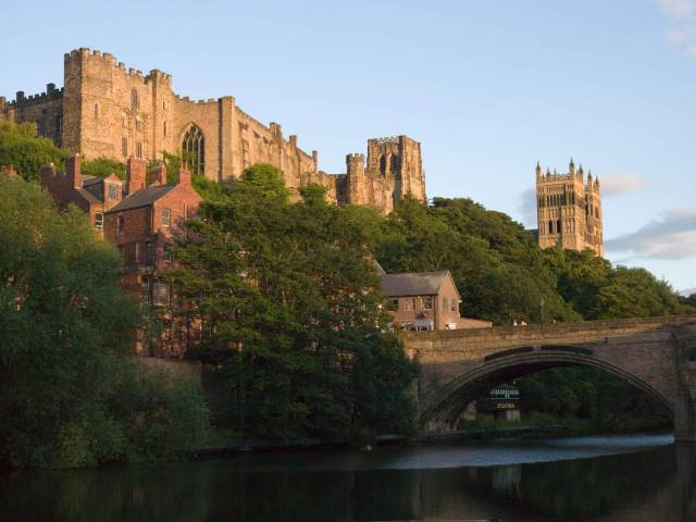 View of Durham Castle and Cathedral on rocky hill, surrounding my leafy green trees