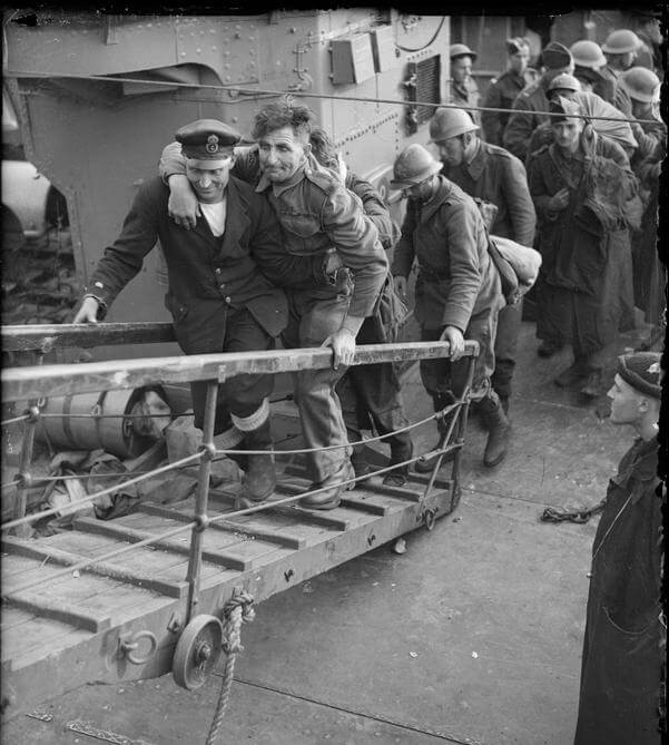 A merchant sailor assists a wounded British soldier up the gangplank from a destroyer, Dover