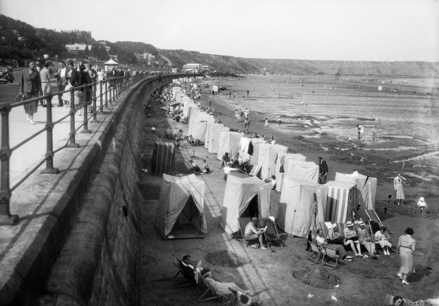 A view looking north along the sea wall at Filey, showing a long line of bathing tents on the beach 1937 © Historic England Archive. Ref: WSA01/01/17504