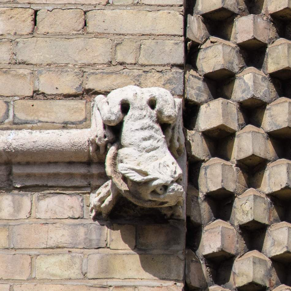 One of two gargoyle-type frogs hanging on the sides of a panel of decorative brickwork, former Criterion Hotel