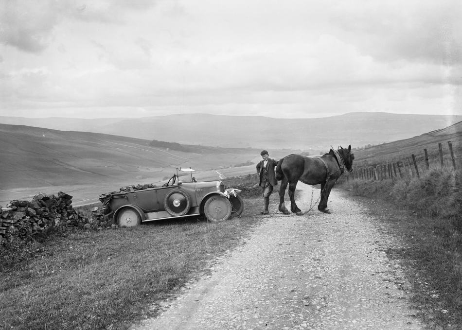A man uses his horse to pull his a car out of a ditch
