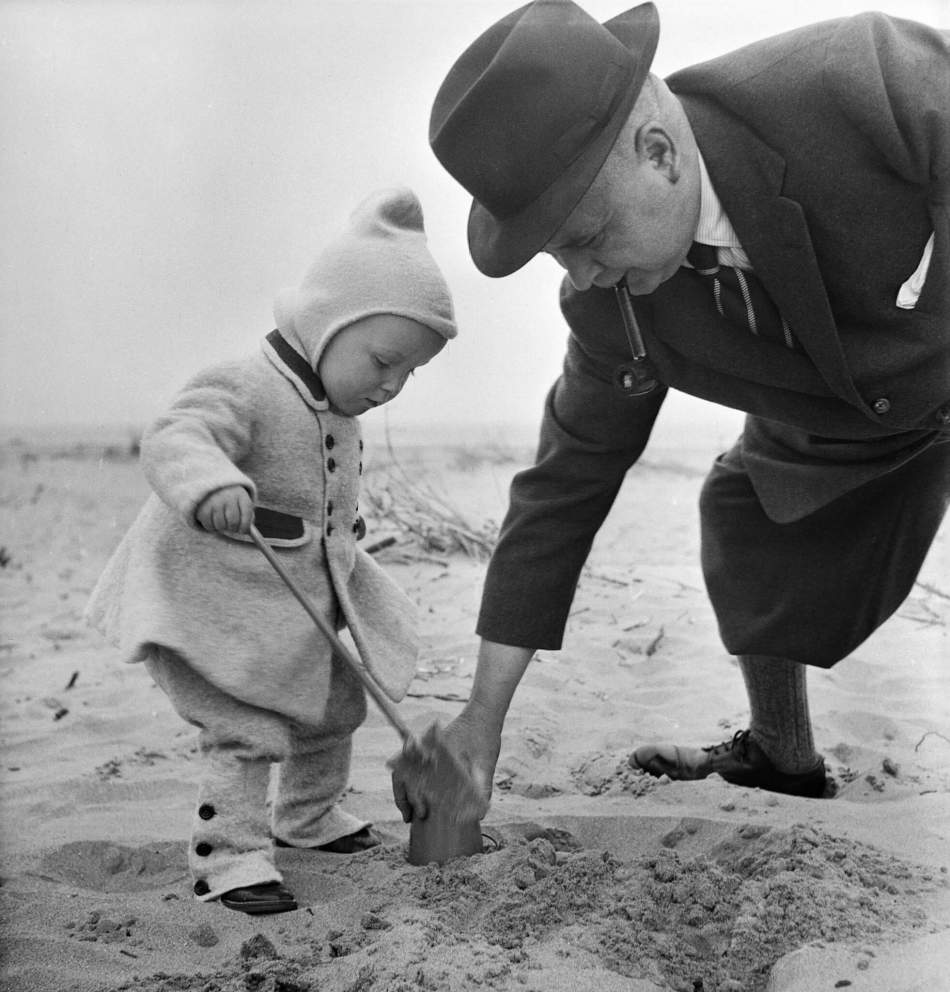 Helping a small boy build a sandcastle on the beach during a staff outing to Skegness,