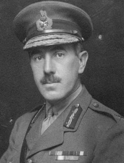 Black and white head and shoulders portrait photo of man in army uniform.