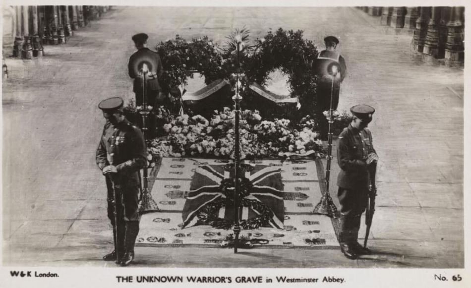 Black and white photo post card of the Unknown Warrior's grave dressed with floral tributes, embroidered funeral pall and union flag in Westminster Abbey.