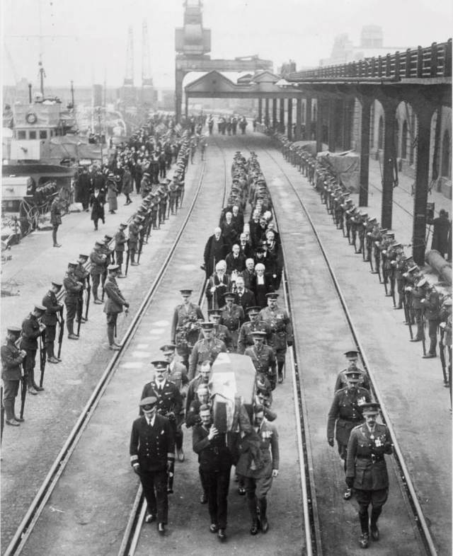 A cortege bringing the coffin of the Unknown Warrior ashore walk between train tracks which are lined either side soldiers standing with heads bowed.