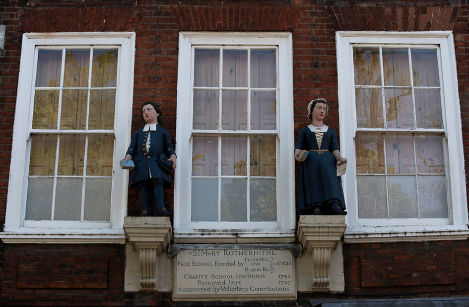 Boy and girl charity scholars, wearing clothes dating from around the 1700s, on the former Rotherhithe Charity School
