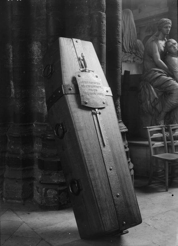 Wooden coffin with metal bands, sword and shield set standing almost on end with stone column and marble statues behind.