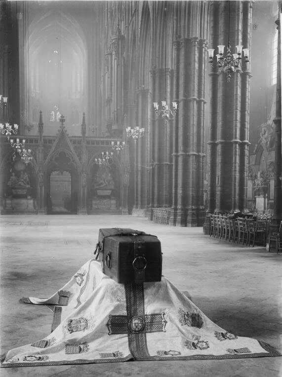 The coffin rests alone in the foreground, with the abbey's impressive architecture stretching upwards around it.