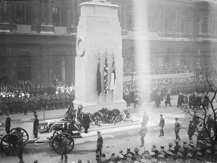 Black and white photo of military lined up at the Cenotaph as crowds of public look on.