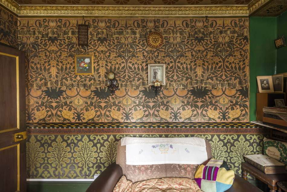 A photograph showing a wall of the drawing room in the David Parr House. The walls are intricately decorated in a dark green and orange-toned floral print.