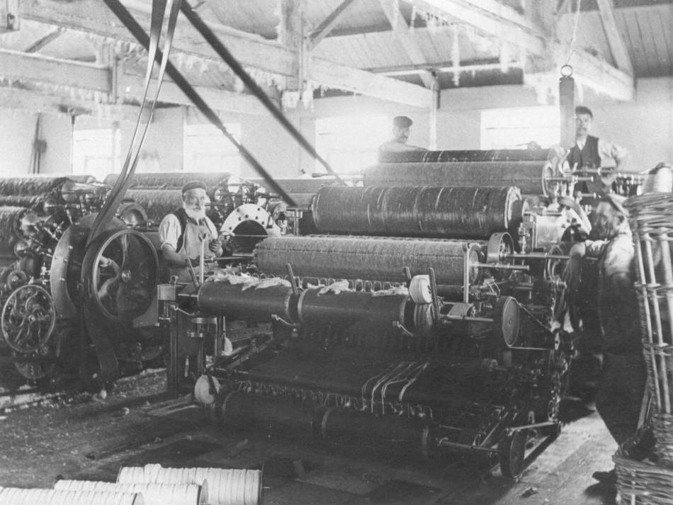 Factory workers operating a carding machine at Early Blanket Mill