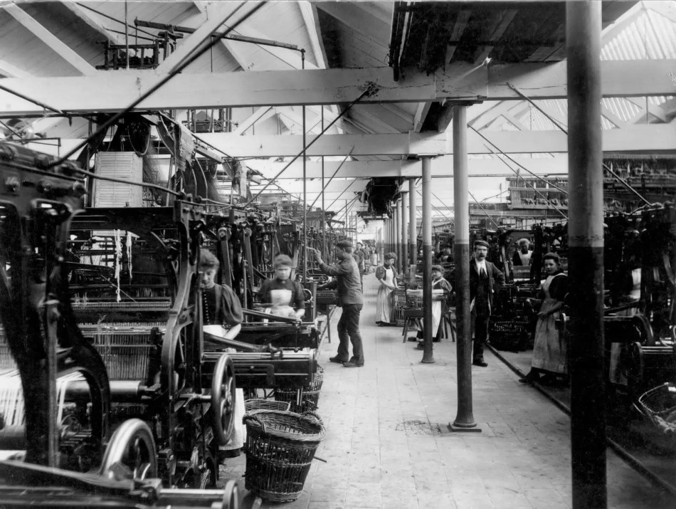 Workers operating heavy machinery in the power loom house