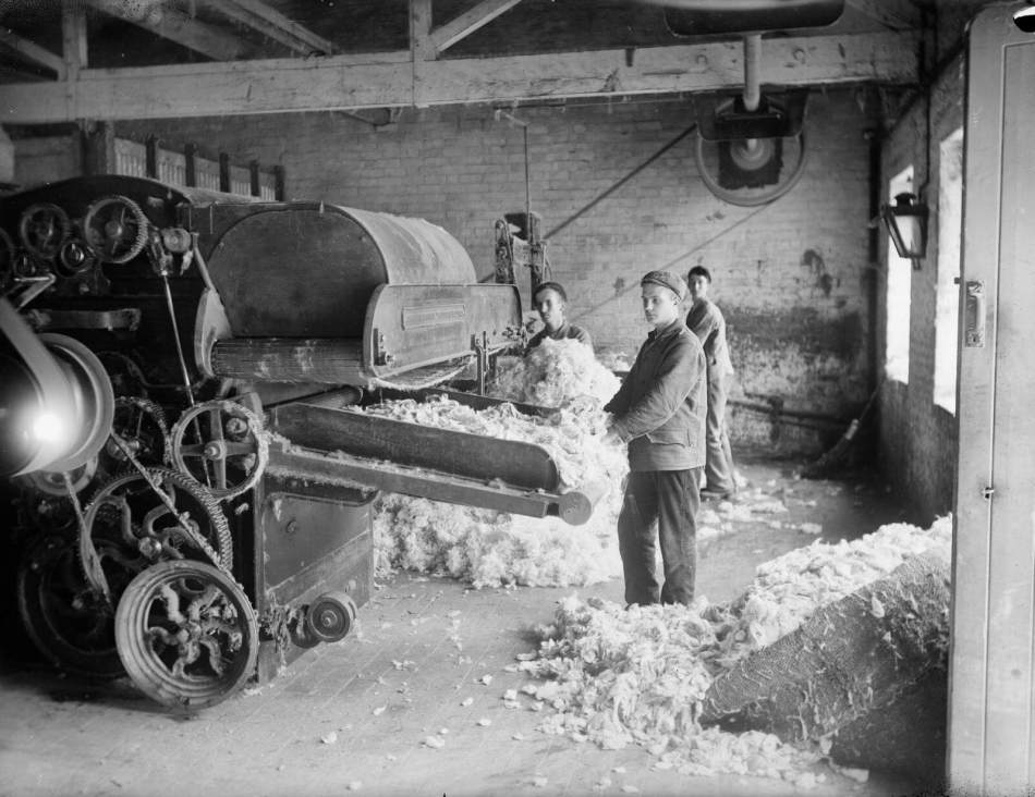 Mill workers attending a machine