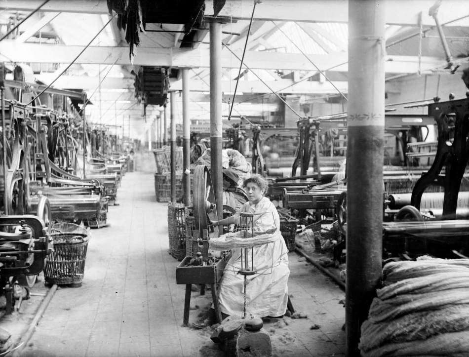 Young woman winding bobbins on wheel in the loom shop