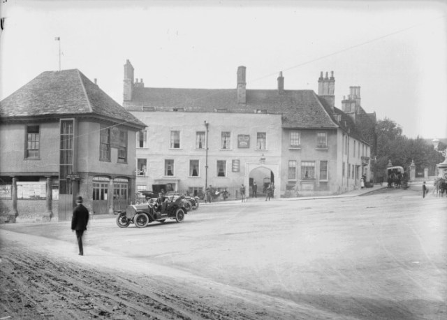 Black and white image of The Market Place and Town Hall in Faringdon with a few cars and a person facing away from the camera