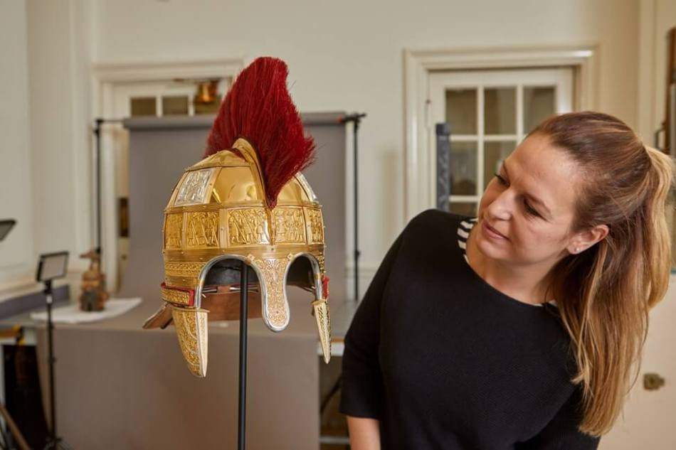 A woman inspecting a reconstruction of a richly decorated Anglo-Saxon helmet.