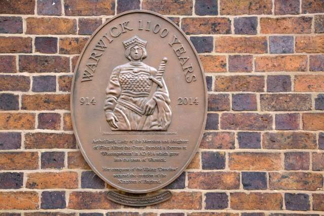 A modern plaque with a depiction of Aethelflaed as a crowned, carrying a sword and wearing armour.